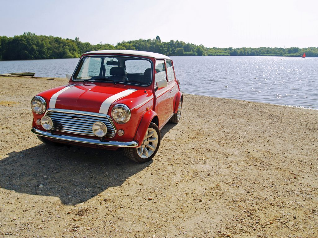 Classic red mini parked next to a lake