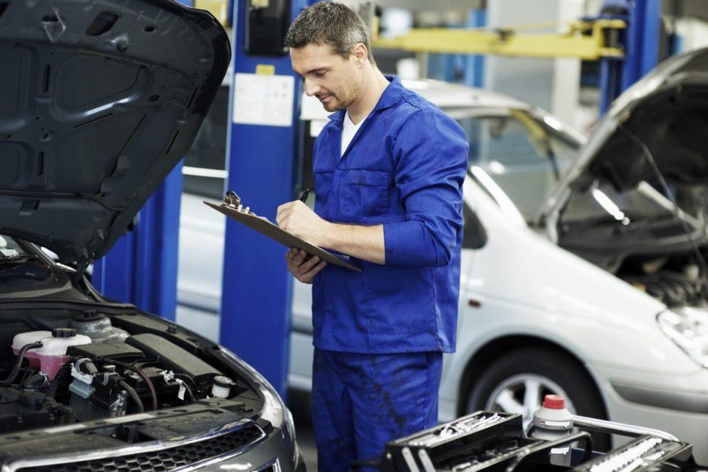 Mechanic making notes for MOT test