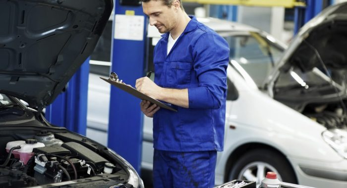 Mechanic making notes on failed mot